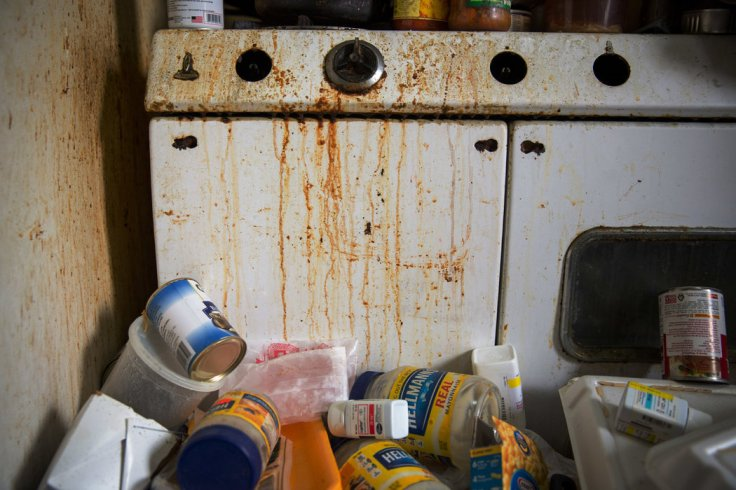 The kitchen was splashed with trash and balled-up lottery tickets, decades old, that failed to deliver. The faucet did not work. The chipped stove had no knobs and could not have been used to cook in a long time. Credit Josh Haner/The New York Times